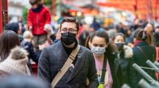 People wearing face masks, walking along busy thoroughfare