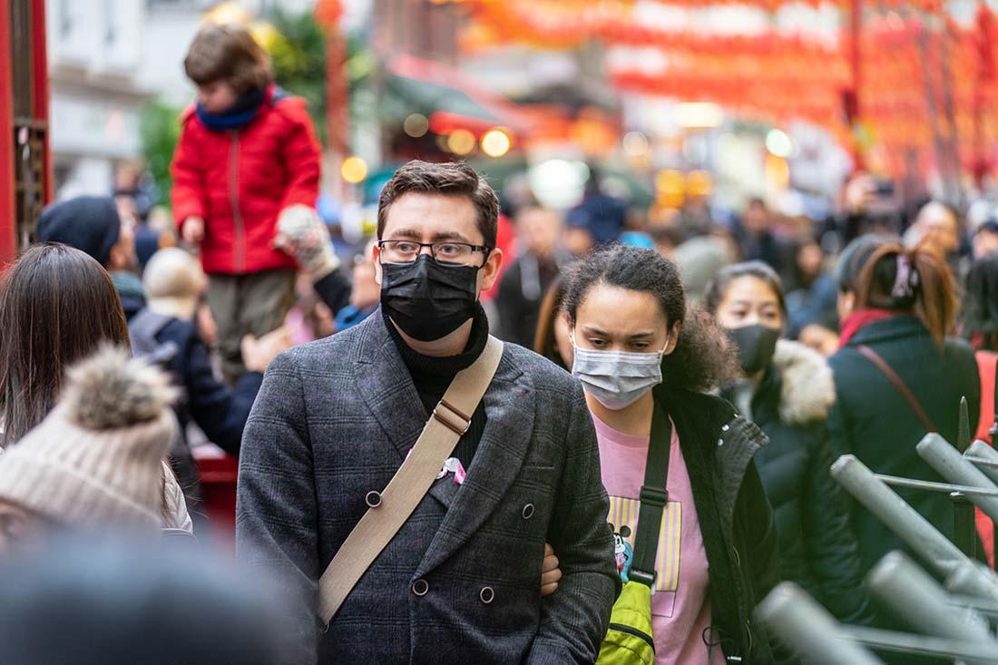 People wearing face masks, walking along busy thoroughfare